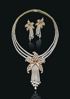 'ORCHID' PARURE BY CARTIER: Comprising a brilliant-cut diamond three-row necklace suspending at the front a detachable sculptural calibré-cut ruby and pavé-set diamond orchid flower with a brilliant-cut diamond tassel pistil (can be worn as a brooch), and a pair of ear pendants en suite, 1989.