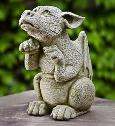 """With sad, """"feed me"""" eyes, this little dragon is crouched with his little arms up, asking for table scraps!  Cast from solid concrete with extreme detail, this sweet baby dragon statue has an English moss-colored finish."""
