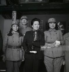 Mme. Chiang Kai-shek, wife of the Generalissimo of the Nationalist Chinese forces, poses with two Chinese Army 'WACS' during a visit to Kinmen Island. Lying a short distance off Communist-held Amoy Island, Kinmen was the object of an invasion attempt last October. Mme. Chiang has been operating like a one-woman U.S.O. in her visits to Nationalist troops. LICENSE