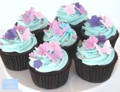 Chocolate cupcakes with light blue frosting, and gorgeous lavender and purple butterfly and flower decorations