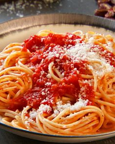spaghetti pomodoro...we love italian food2 tablespoons extra-virgin olive oil, plus more for drizzling 2 cloves garlic, finely minced Pinch of red pepper flakes 1 28-ounce can best-quality whole tomatoes, lightly pulsed in a blender 1/2 teaspoon salt Freshly ground black pepper Small pinch of sugar 1 sprig fresh basil 1 pound spaghetti Freshly grated Parmesan cheese