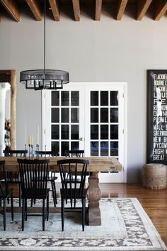 Amazing architectural details and great bones call to be enhanced with rich industrial finds mixed with eclectic, modern touches. A long, rustic dining table is surrounded by a mix of vintage chairs all painted black.