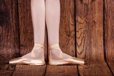 The first position in classical ballet. Slender legs of a ballerina in pointe shoes. Photo closeup.