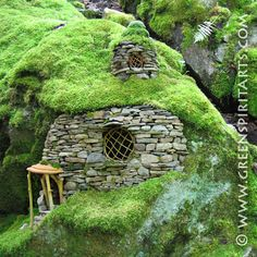 "The Emerald Mossy Fairy House (built by Sally J Smith) took a week to build... 2 of those days were spent gathering the stones and bringing them in to the site. The large mossy boulder-cliff already looked like a house in Sally's eyes...""it just needed a little encouraging to bring it out!"" A Weeping Willow twig twisted to make the large window. A shelf fungus as an awning to protect the entrance-way. A small dormer room was added later. The stone walling portion is approx 30"" high."