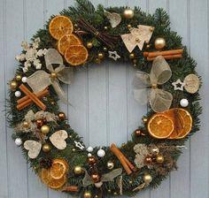 Ghirlanda natalizia composta da rami di abete addobbati con palline di natale, rametti di cannella e agrumi