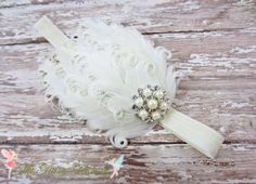 This headband consists of stunning curled ivory nagorie feathers accented with a pearl and rhinestone embellishment. The feathers are