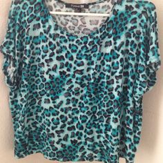 Turquoise animal print shirt A soft turquoise shirt with animal prints spiraled from front to back. The sleeves are very short. A little see through, but not enough to see your undergarments. No flaws and worn once. ALWAYS OPEN TO NEW OFFERS✨ Forever 21 Tops