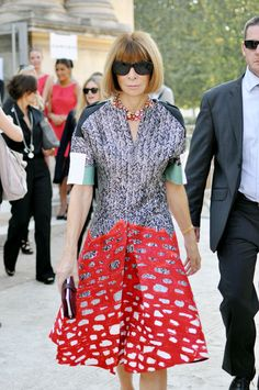 Anna Wintour wearing a printed dresswith statement necklace and simple small clutch bag