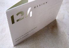 124 Design Business Card  Modern business card features a die cut logo and foldable design.