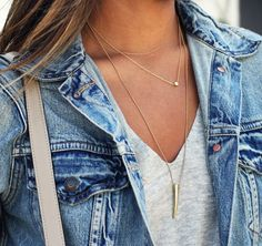 Layered gold necklaces, grey v-neck, and a denim jacket.