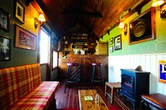 The Shebeen Mobile Irish Pub. Fully functioning bar, seating for 10 & sound system. Green walls. White paneling. Bar stools. Plaid wrap around sofa. Small fireplace. Whiskey sign. Framed photos. Coffee table. Wood floor.