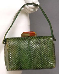 Green cobra box purse with a gold toned and bakelite clasp.