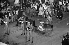 The Beatles 1964 US Tour, Paul McCartney, John Lennon and George Harrison of the British pop group The Beatles singing on stage during one of two concerts they performed at Carnegie Hall in New York on 12th February 1964.