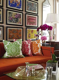 If you love color, flaunt it! The art works because the frames & mats are all the same & the way they are hung draws attention to the art itself. The colored pillows, sofa & even the orchid reinforce the focal point of the art.