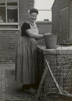 Vrouw in Walcherse streekdracht uit Westkapelle. De vrouw is gefotografeerd bij de regenwaterput en is gekleed in werkdracht. 1950 #Zeeland #Walcheren