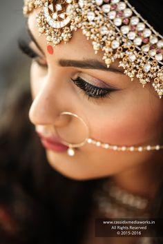 Bridal Makeup - Bride Wearing a Gold Choker with a Red Stones and Bronze Makeup, Gold Jewelry Tikka. WeddingNet #weddingnet #indianwedding #makeupandhair #weddingmakeup #weddinghair #hairbun #maangtikka #jewelry #goldjewelry