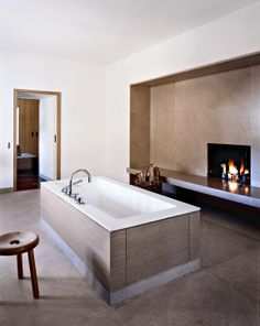 a boxed bathtub and fireplace with drawers/cabinet on either side
