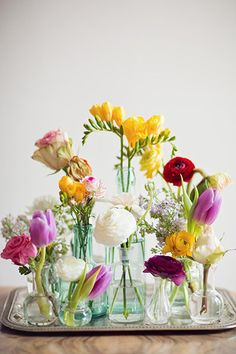 Flowers - A simple grocery store bouquet gets a makeover when you stagger the stems in many small vases.