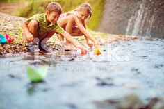 Boy and girl playing paper boats on the river royalty-free stock photo