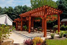Custom artisan wood pergolas with cedar-wrapped posts and privacy panels http://www.backyardunlimited.com/pergolas