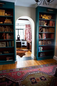 Turquoise bookshelves, Oriental rug.
