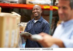 Manager In Warehouse With Worker Scanning Box In Foreground - stock photo