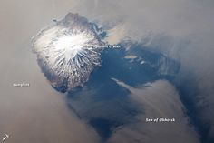 The Kuril Island chain extends from the Kamchatka Peninsula to Japan and contains numerous active volcanoes along its length. This astronaut photograph highlights Alaid Volcano, the highest (2,339 meters above sea level) volcano in the chain, as well as the northernmost. The textbook cone-shaped morphology of this stratovolcano is marred only by the summit crater, which is breached to the south (image center) and highlighted by snow cover.