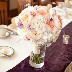 On the reception tables, flowers in vases served as the centerpieces. This particular arrangement had white, ivory, and soft pink flowers with touches of purple. Photo Credit: The Salty Peanut