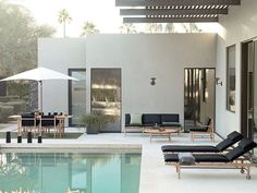Love this simple, white, boxy home with black exterior seating and that clean edged pool