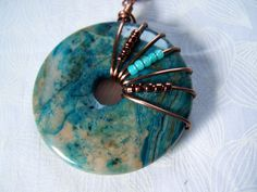 Donut Pendant Copper Wire Wrapped Agate Necklace Boho This beautiful pendant is made from a 50mm blue/beige agate donut wrapped with antiqued copper wire which is embellished with brown and aqua seed beads to match the stone. The chain is 20 long and is antiqued copper wheat chain
