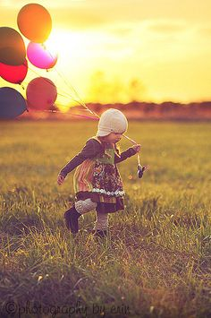 Little girl running down the green pasture with a lots of balloon