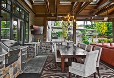 This outdoor living area is perfection. The ideal place to enjoy a mini staycation during summer because with a space like this who would ever want to leave? This outdoor living area has a custom fit chandelier, grill station, entertainment area, a full length dining table and weather-proof couches.  Sammamish, WA Coldwell Banker BAIN