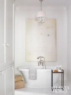 Chic bathroom features abstract art over a roll top tub paired with floor-mounted vintage style tub filler beside an iron bath table atop white marble floor illuminated by a Barbara Barry Westport Chandelier.