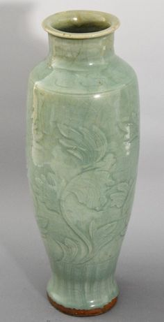 CHINESE CELADON GLAZED PORCELAIN VASE. Longquan celadon glazed baluster vase carved with a flowering peony branch band above vertical comb marks encircling the walls and visible beneath the crazed sea green glaze. H 34.5 cm