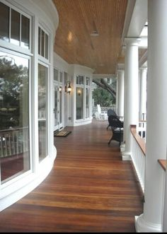 wide wrap around wood veranda on double bow fronted building