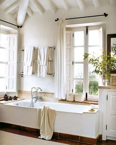Bathroom with low tub, high ceilings, tall windows - in the La Huerta El Noque villa in Andalucia.