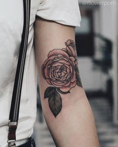 Illustrative pink rose tattoo on the left bicep.