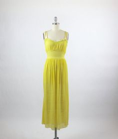Vintage 1930s - early 1940s gown set  Stunning vintage set in a crinkle silk crepe :: Vivid yellow with green smocking / embroidery :: Lovely full-length gown with double narrow straps :: Gathered bust, wide waistband with ties in the back to adjust the waist :: Fully gathered skirt with lettuce hem  Matching dressing gown with dramatic ruffled collar :: Smocking with inset pearl beads :: Long sleeves with smocking & ruffles at the cuffs :: Tiny buttons at the neck :: Open flowing de...