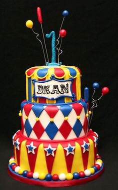 This blue, red and yellow boy's first birthday party circus cake features classic birthday patterns.