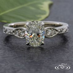 Design Your Own Unique Custom Jewelry at Green Lake Jewelry Works! Custom Platinum engagement ring with Oval diamond center stone and tear drop tapered bead set diamonds on side with milgrain edge. top face with hand engraved scroll work.