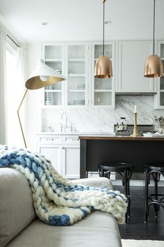 open layout kitchen and living room. white cabinets with carrera marble backsplash, brass pendant lights, and black island. light grey couch with chunky white and blue throw blanket.