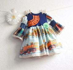 """Toddler girl's, navy, blue and orange, train theme dress in size 3T made from vintage fabric. Eco-friendly clothing for the prairie girl at heart by My Fair Maiden featuring re-purposed fabrics and trim. All lovingly sewn by hand. (mine!)""""SARAH"""" DressThis one of a kind dress was made using vintage fabric with train images. On the navy blue bodice, I've created train tracks with fabric and yarn. The sleeves are princess style with puff shoulders and bell in plaid. At the waist is a mint green…"""