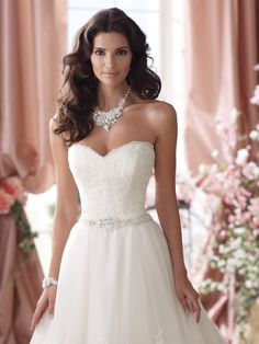 This lace and tulle ball gown wedding dress, features a sweetheart neckline with eyelash trim, soft embroidered lace bodice and softly curved back bodice