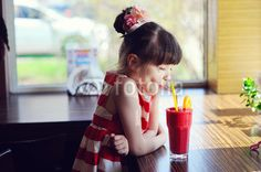 Child girl drinking strawberry smoothie