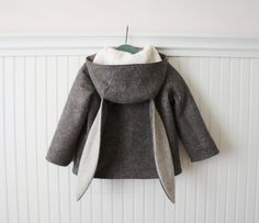 The Flopsy Bunny Coat is a charming companion for cooler weather. This boys winter coat is made from heather brown 100% wool felt with a body lining of organic cotton sherpa. The front closes with buttons beneath two toggle fasteners, and two welt pockets warm chilled fingers or store treasures found on walks through the forest!  A great companion coat to our Snowshoe Rabbit, for siblings, besties, or twins!  Snowshoe Rabbit Coat: https://www.etsy.com/listing/243239922&#x2...