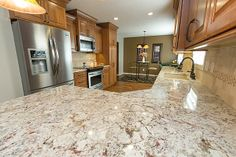 Designers: Laura (cabinets, countertops), Bill (flooring) Cabinets: Dura Supreme Cabinetry Cherry Arcadia Classic Door in butternut  Granite: White Persia Backsplash: Ivory 3x6 Tumbled Travertine with Fidenza deco  Flooring: Chalet Maple Tremblant Appliances: Frigidaire and Electrolux