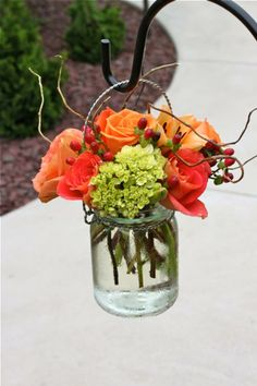 "Roses, thin twiggy vines, not sure what the green and ""berries"" are but love the hanging jar display."