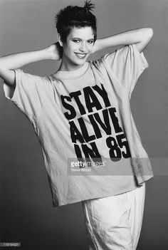 A model wearing a large t-shirt with the slogan 'Stay Alive in 85', December 1984.