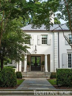 Off-center entryway is given greater presence by recessed door and columns - love the lantern - love the doors