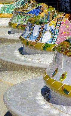 The upper level of Antoni Gaudi's Parc Guell. The mosaic serpentine benches colorfully wind themselves around the perimeter of the large public outdoor space.  Barcelona, Spain.  by Alan Todd